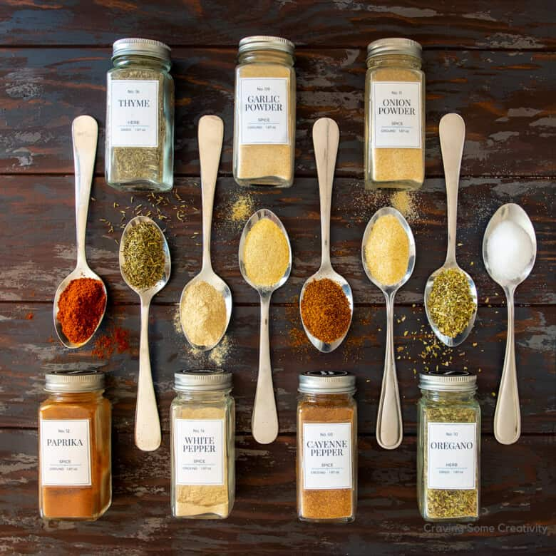 Spice bottles laid out with spoons on a wood background.