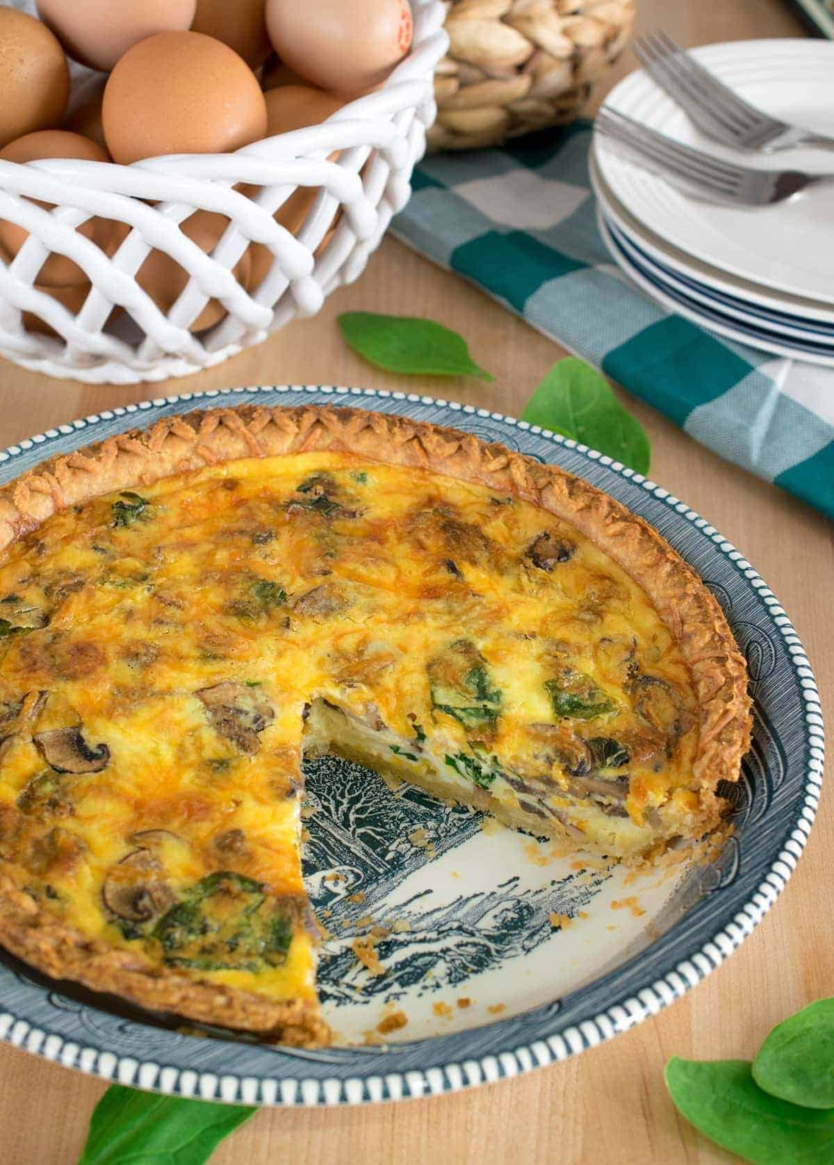 Spinach and mushroom quiche with crust in pie plate with one missing piece. Basket of eggs and stack of plates in background.