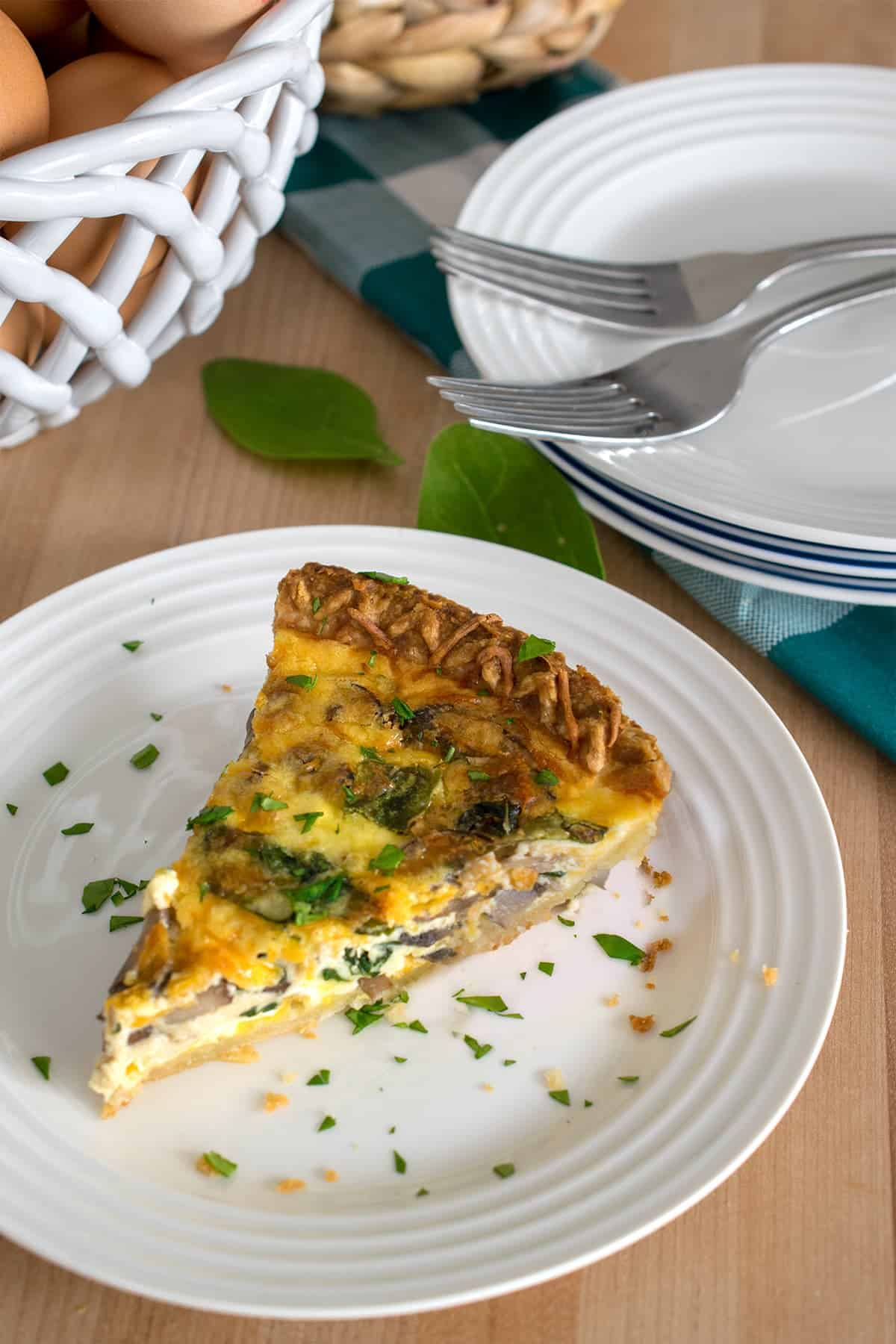 Spinach and mushroom quiche slice on white plate with stack of plates and two forks behind the main feature.