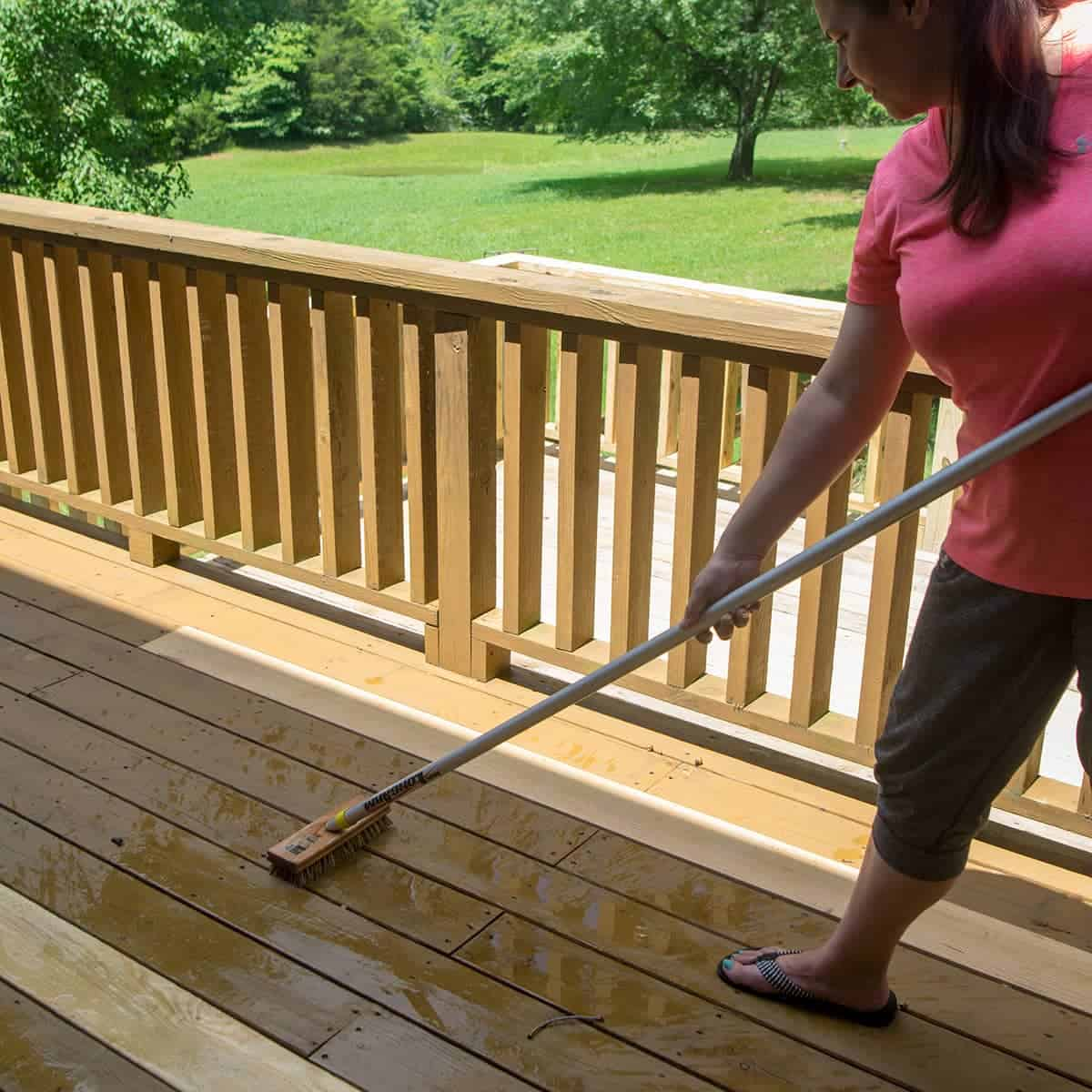 Brushing peeling stain off pressure washed deck with long handled bristle broom.