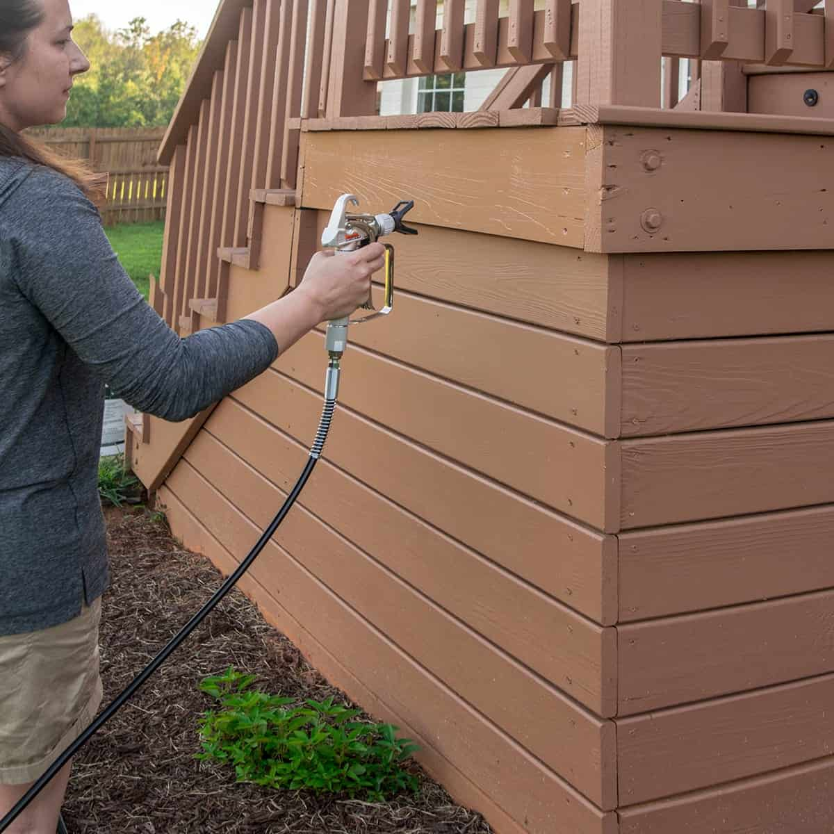 Woman using an airless paint sprayer to paint the wall of a raised deck.