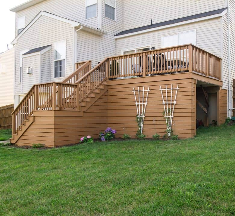 Solid color stained raised deck with shed area underneath.