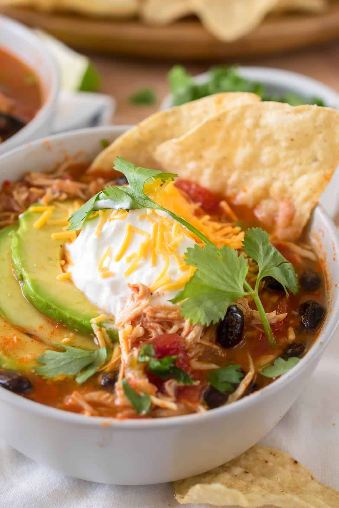 Close up of white chicken tortilla soup with black beans, tomato, cilantro, shredded cheese, avocado and tortilla chip.