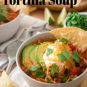 Chicken Tortilla Soup in a bowl topped with sour cream, avocado, cilantro, and cheddar cheese.