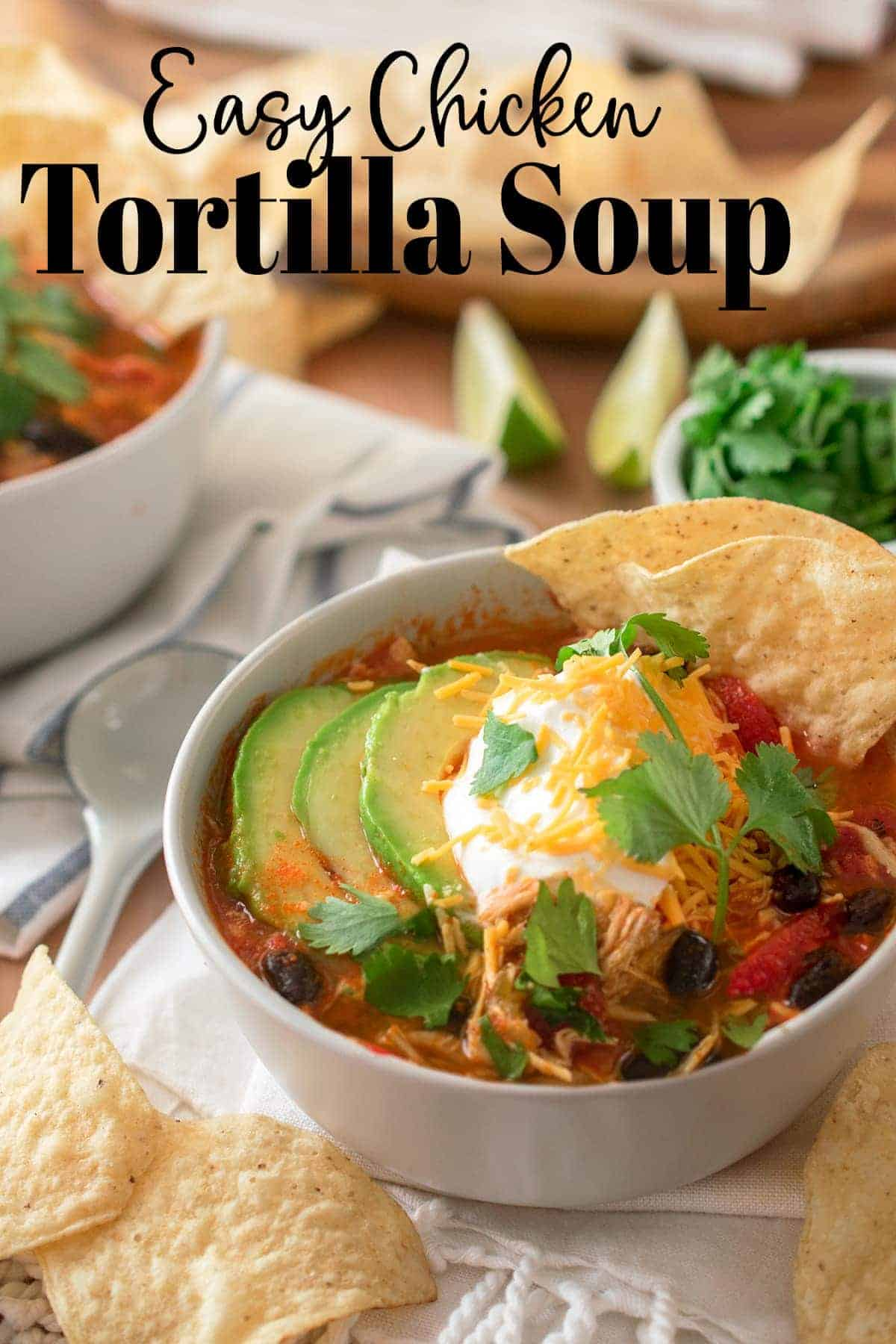 Easy Chicken Tortilla Soup topped with avocado, cilantro, cheese and sour cream with tortilla chips. Ingredients strewn around in the background and forefront.