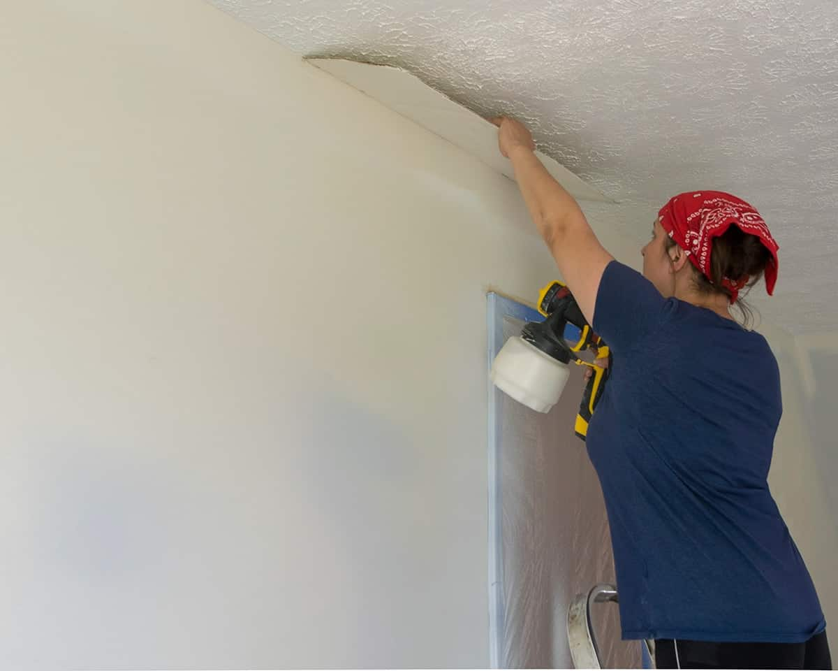 person painting a wall indoors with a paint Sprayer and holding carboard to edge the paint.