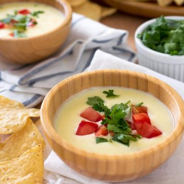 Mexican cheese dip in a small bowl garnished with tomatoes and cilantro.