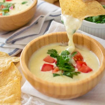Restaurant style Mexican white Cheese Dip with pico de gallo topping in wooden bowl on dish cloth with chips.