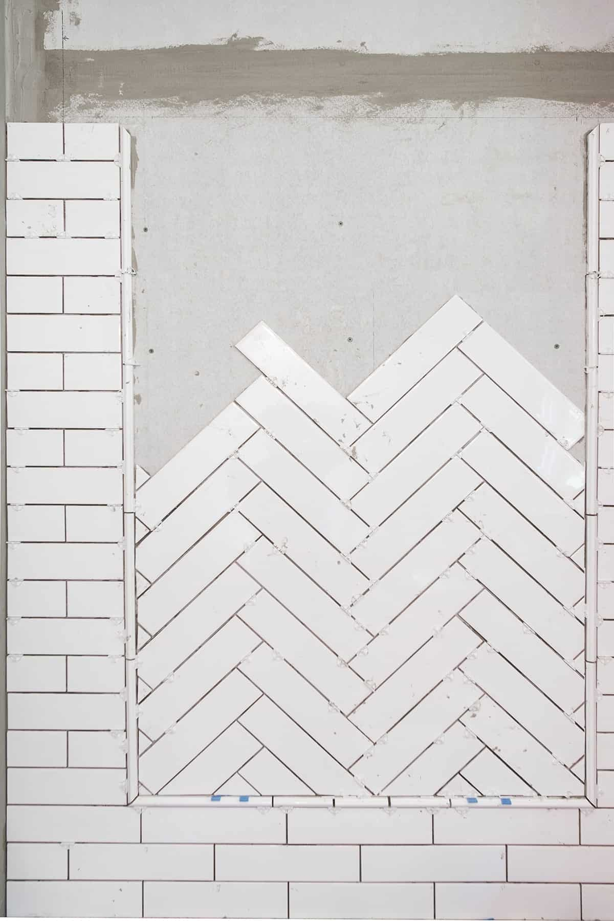 In progress photo of ceramic tile set in herringbone pattern inlay with border surrounded by subway tile shower.