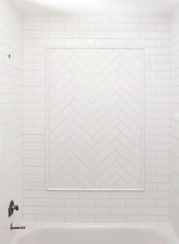 White subway tile shower wall with herringbone inset.