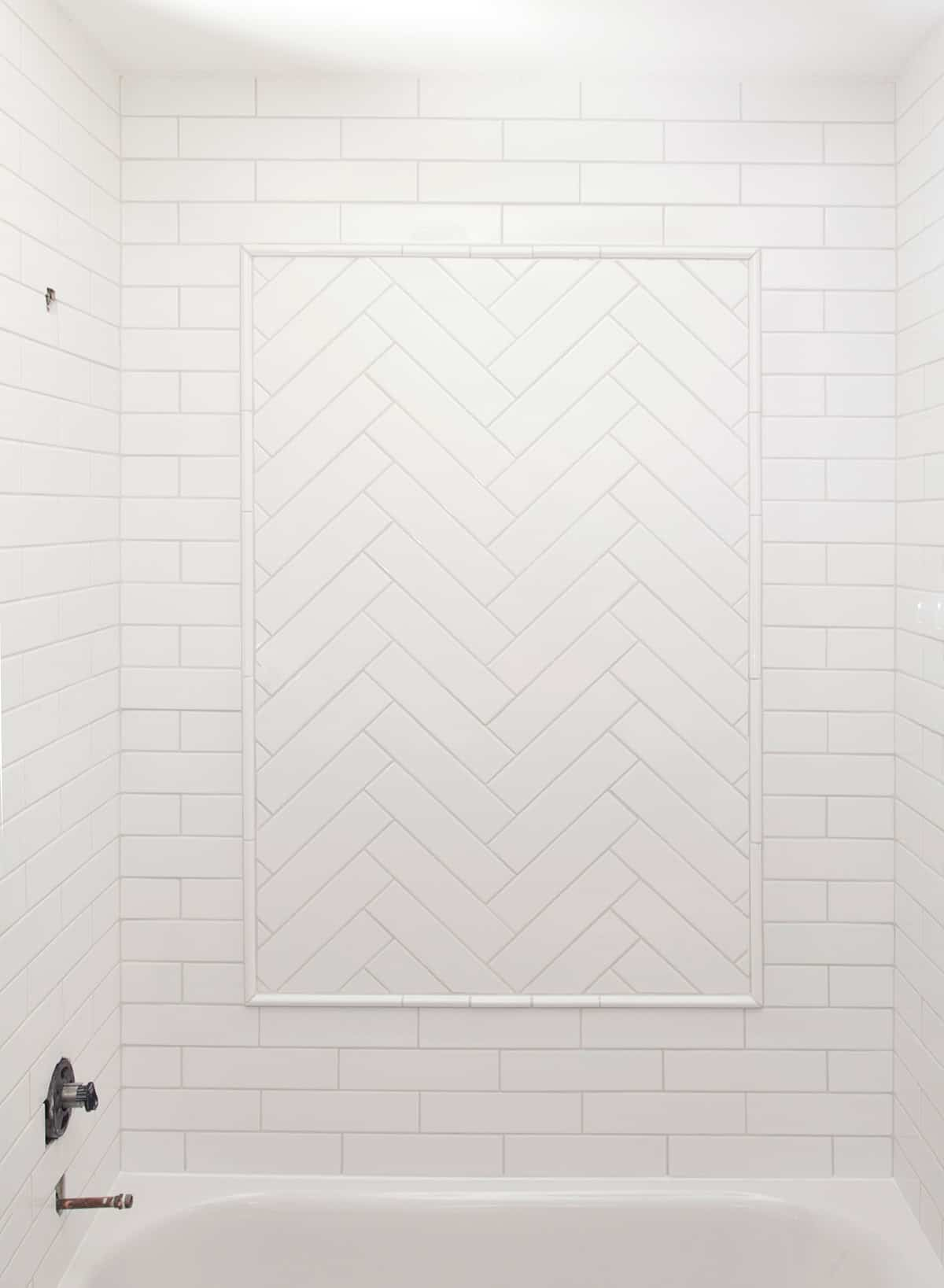 White Herringbone Tile inset Tub surround with subway tile.