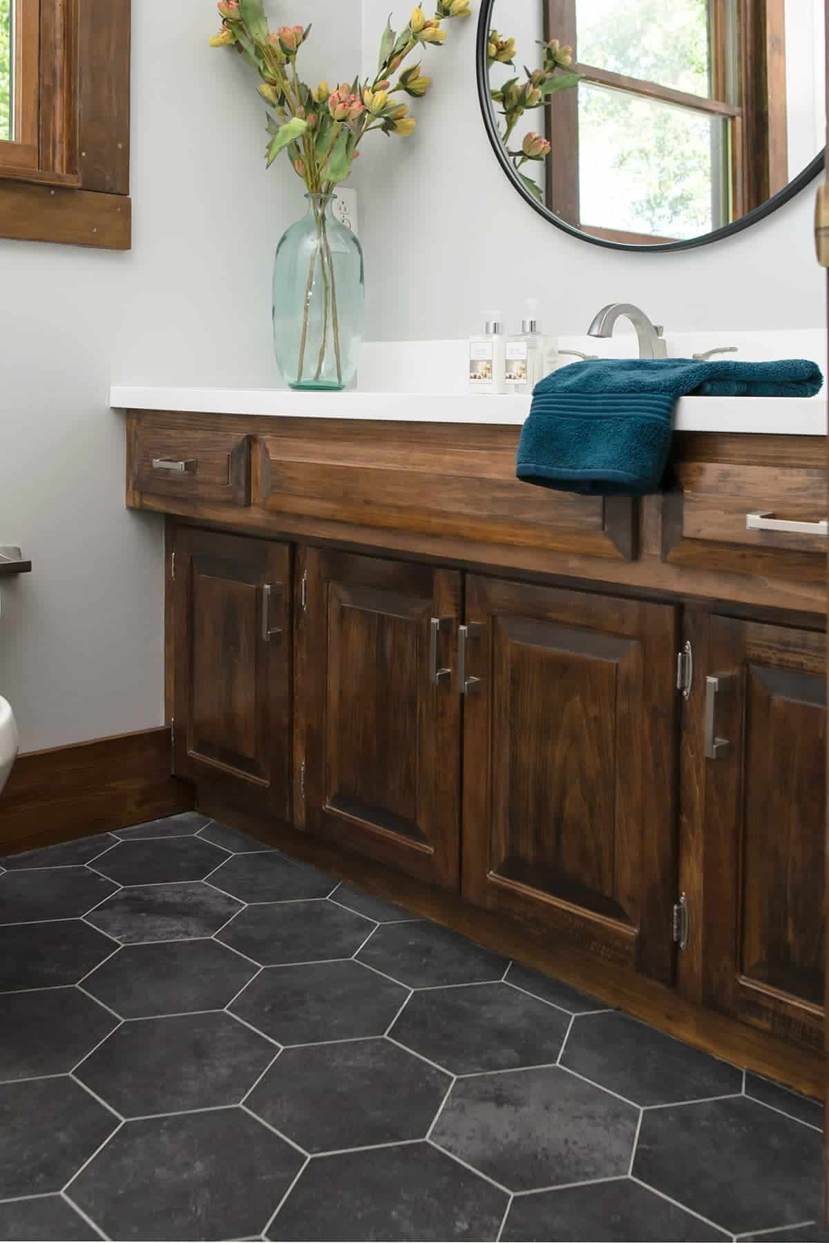 Dark gray groutable vinyl tile in modern farmhouse style updated bathroom.