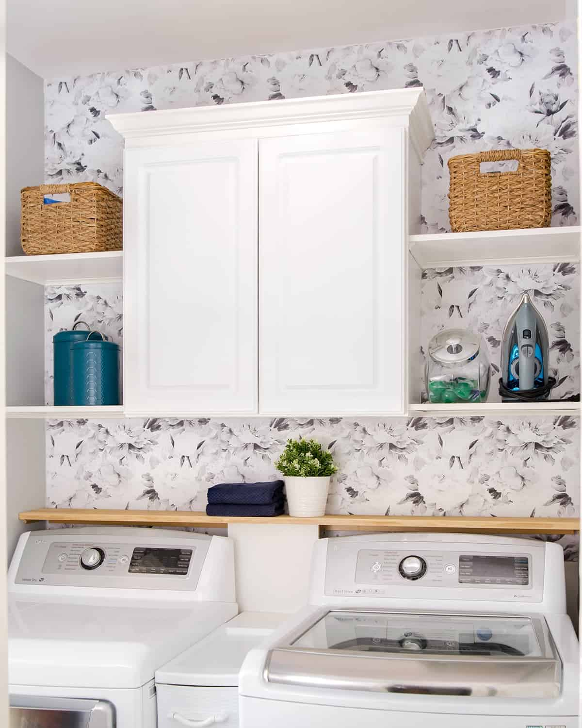 Laundry room cabinet over floral wallpaper. Shelves with basket organizers and coordinating jars and canisters.