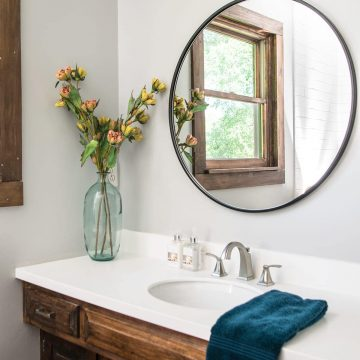 Rustic bathroom with round mirror, white countertop, dark wood cabinets, and gray walls.