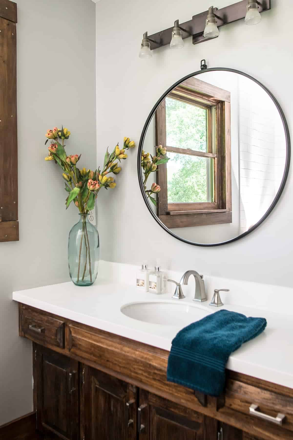 Rustic modern farmhouse bathroom with dark wood cabinets and accents, white countertops and simple neutral decor.