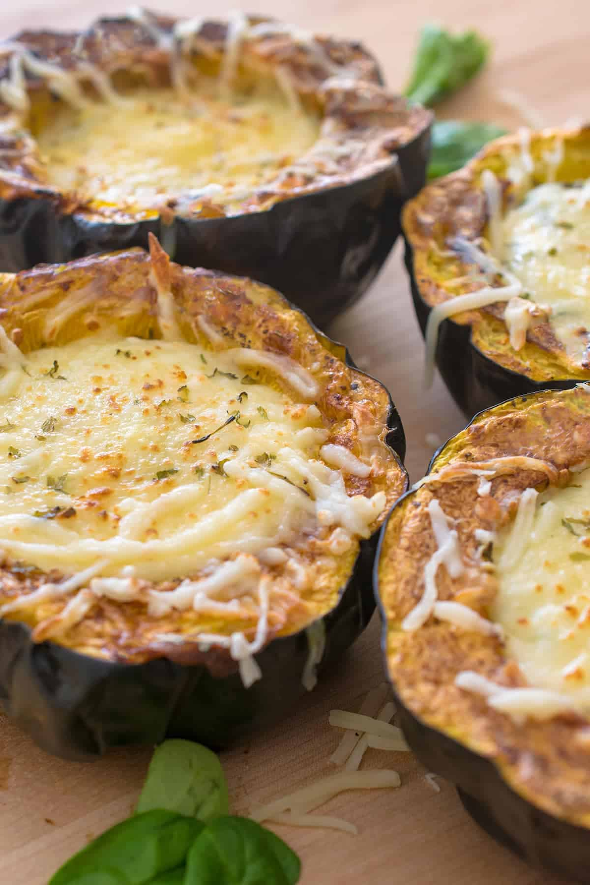 Close up of roasted stuffed acorn squash with spinach dip and cheese.