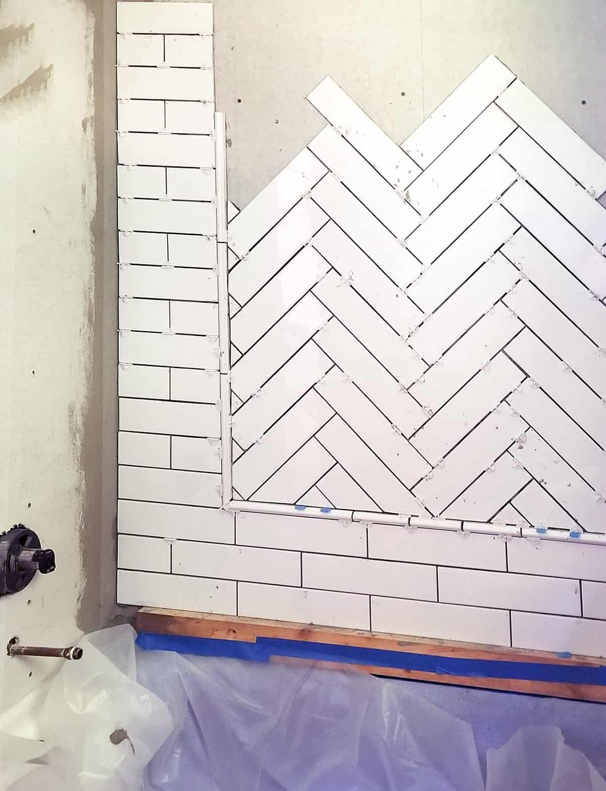 In progress photo of laying herringbone pattern with ceramic tile inset with subway tile surround.