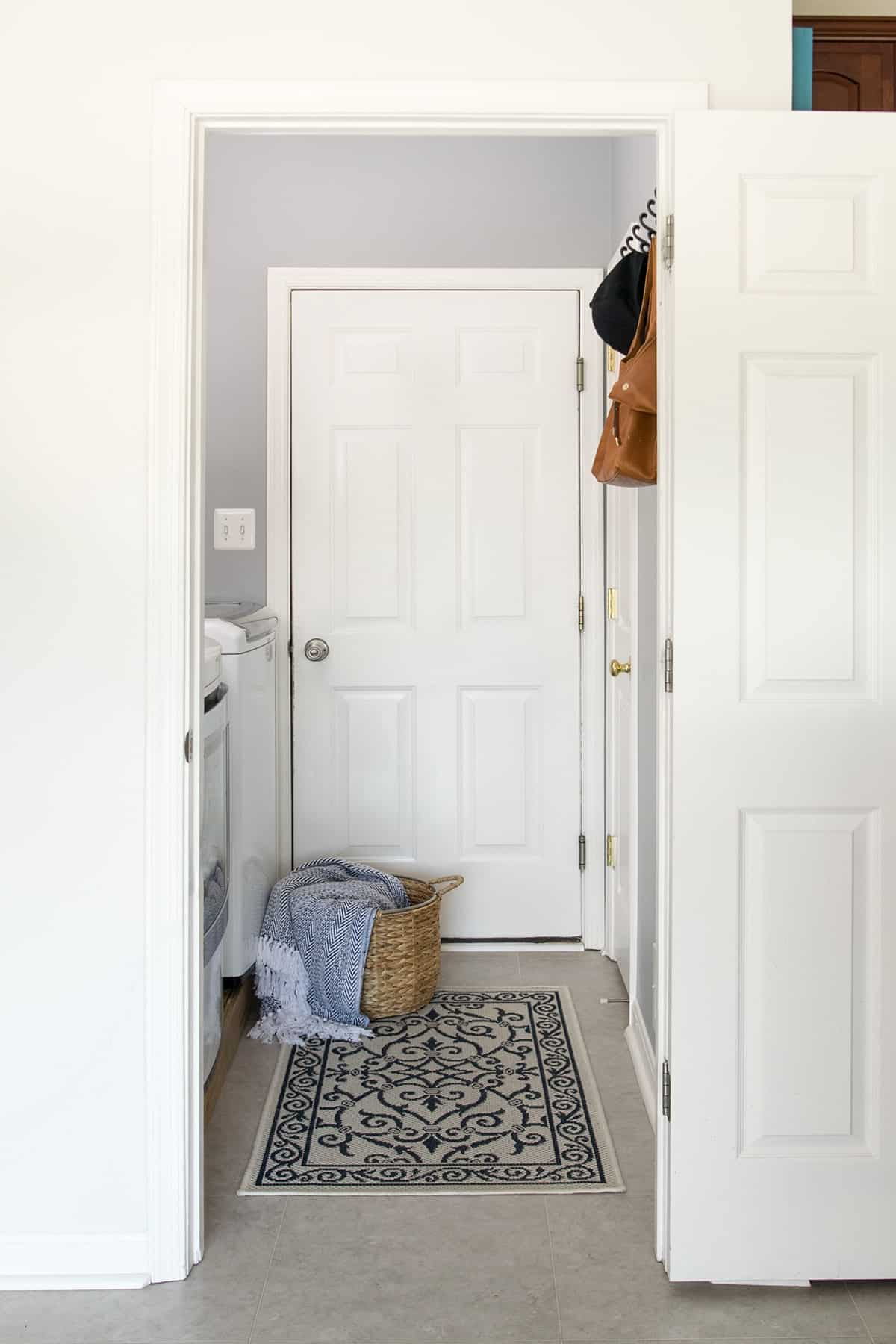 Laundry room entryway. Decorative throw rug rattan basket, gray wall paint.