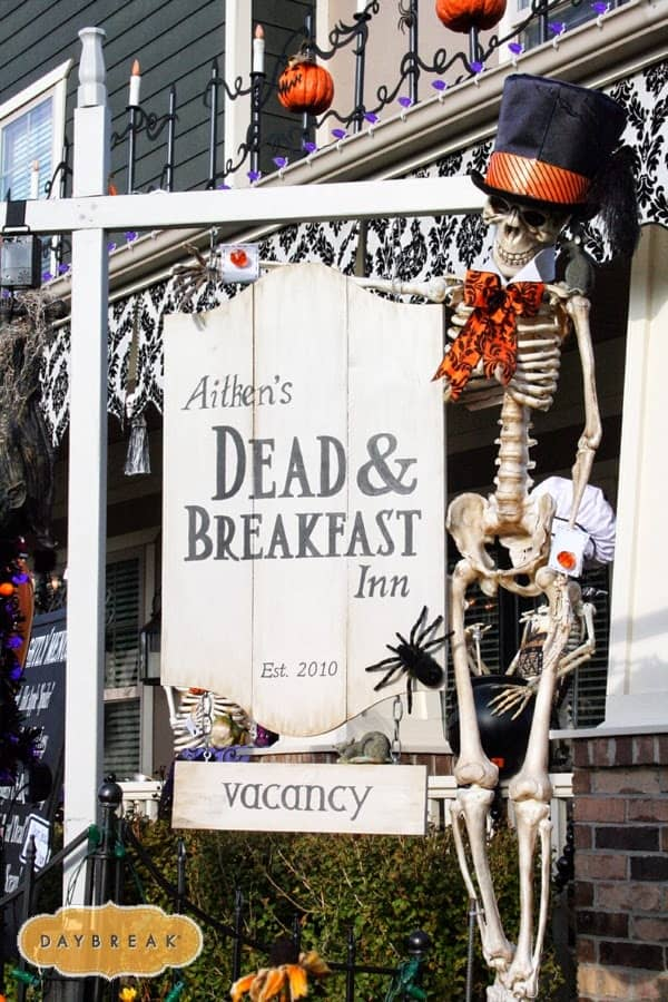 Halloween front porch decor Dead and Breakfast Inn sign with costumed skeletons.