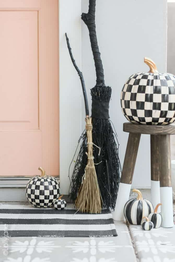 DIY witch broom made with twigs standing next to doorway.