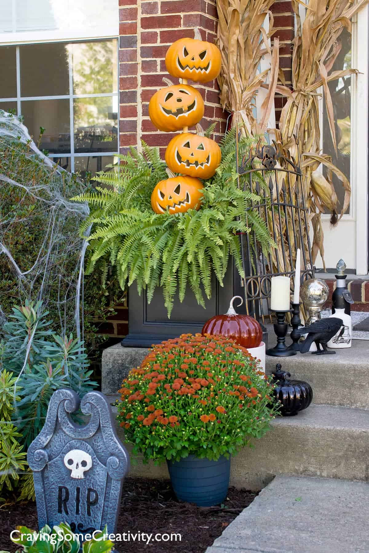 Halloween Front Door Decorations with Pumpkin Topiary, spider web corn stalks and witch potion shoppe decor.