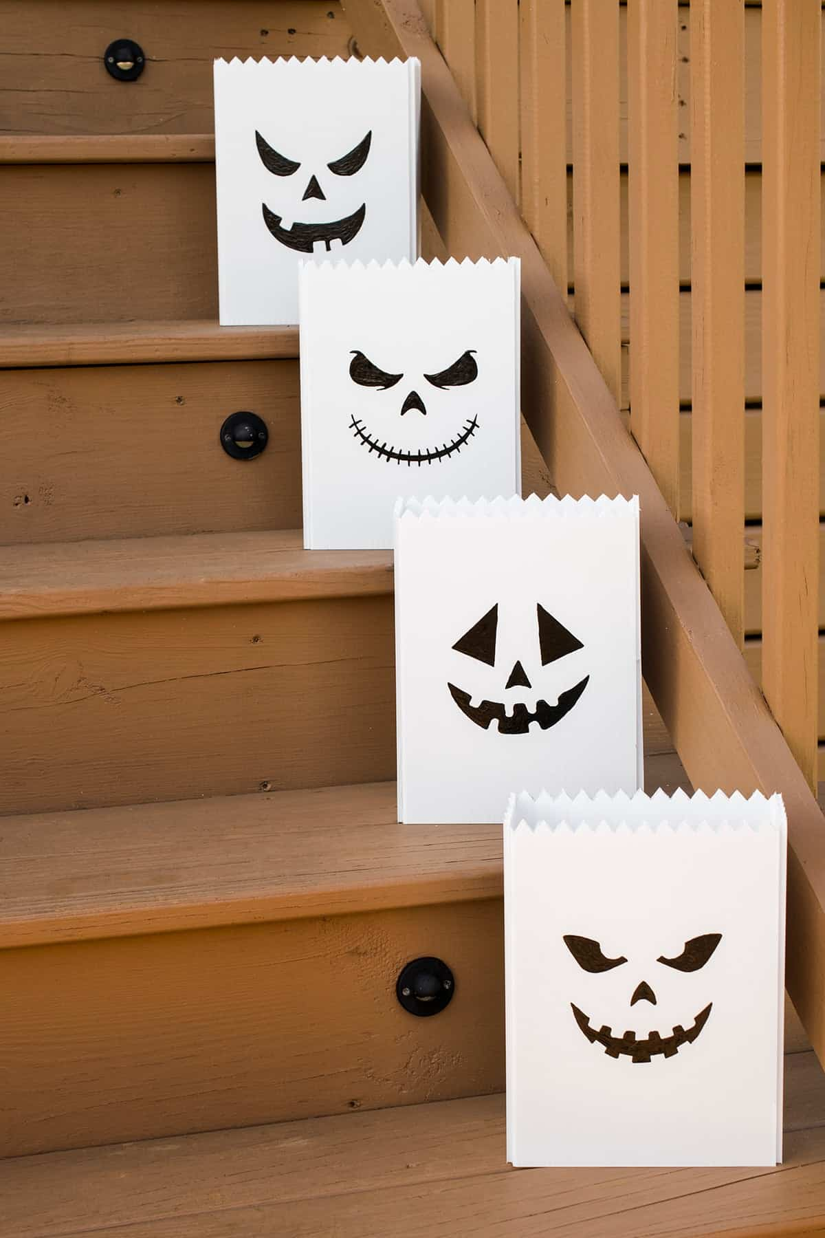 White outdoor pumpkin luminaries with black jack-o-lantern faces on wooden deck steps in daylight.
