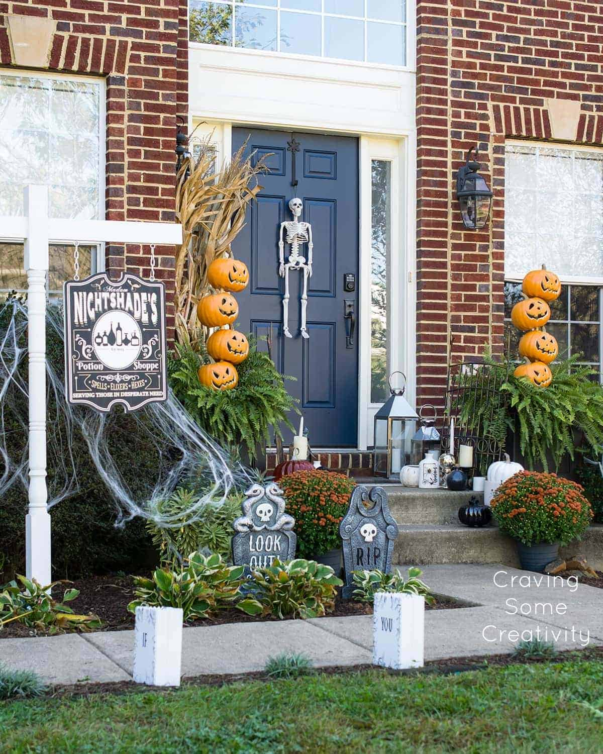Halloween front porch decor. Pumpkin topiaries, DIY Potion Shoppe sign, DIY luminiaries, headstones, skeleton and black and white pumpkins.