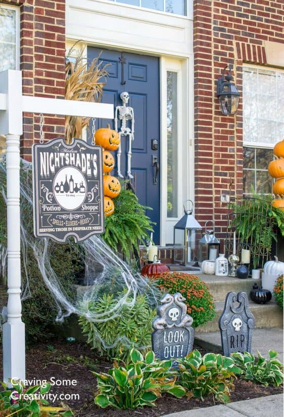 Outdoor Halloween decorations including pumpkins, zombies, graveyard, and a witch house or apothecary shoppe.