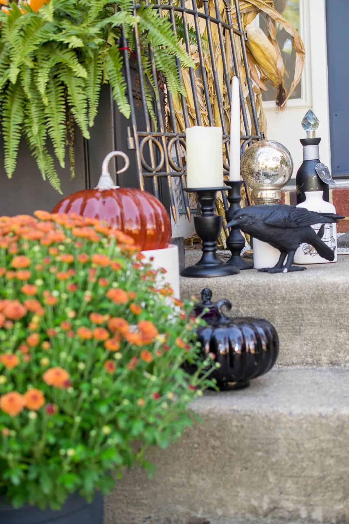 Witch Shop theme front porch with black crow, potion bottles, glass pumpkins and candlesticks.