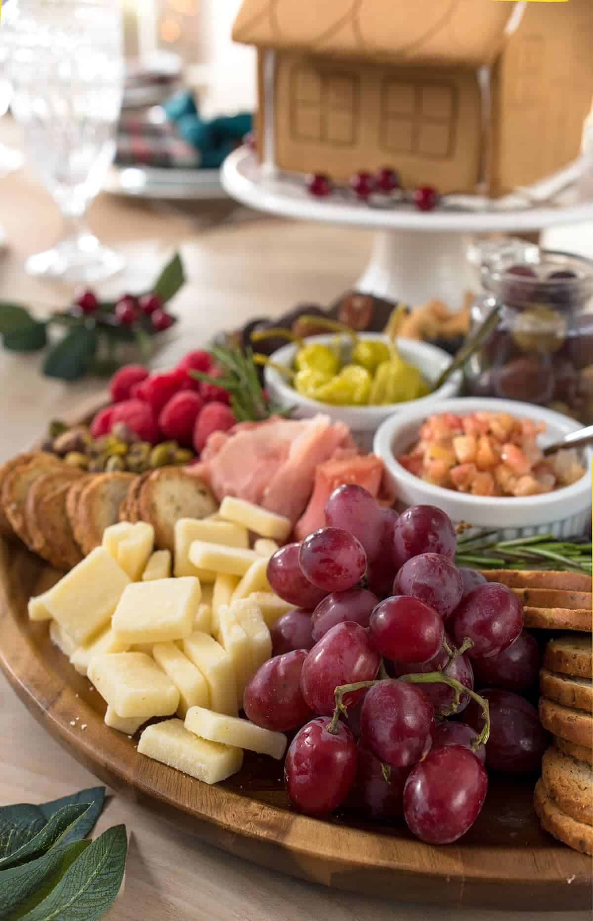 Full charcuterie board on display on dining room table. Close up of grapes, cheddar cheese, bagel crisps, pistachios and bruschetta. Crystal goblet and gingerbread house in background.