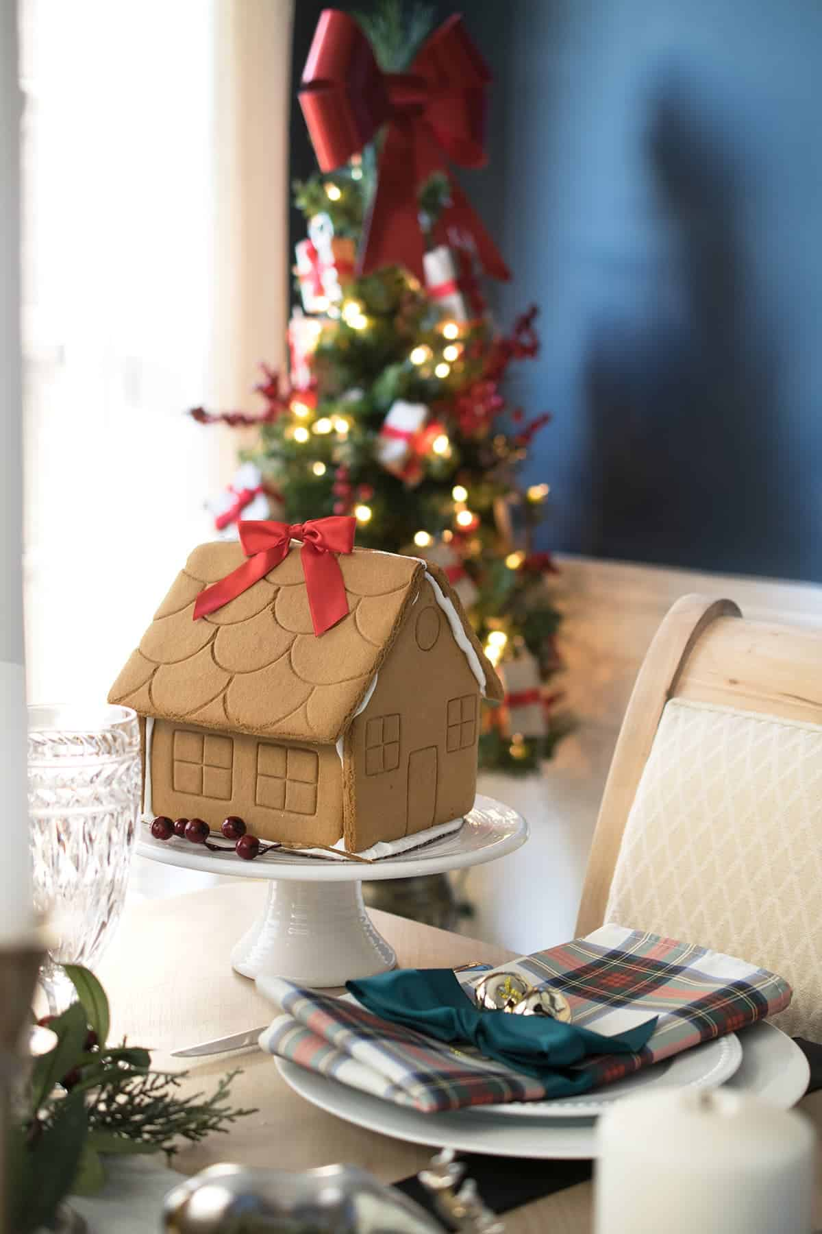 Christmas Table Decoration centerpiece with gingerbread house. Crystal goblets, Tartan plaid napkins tied with green ribbon and jingle bell.