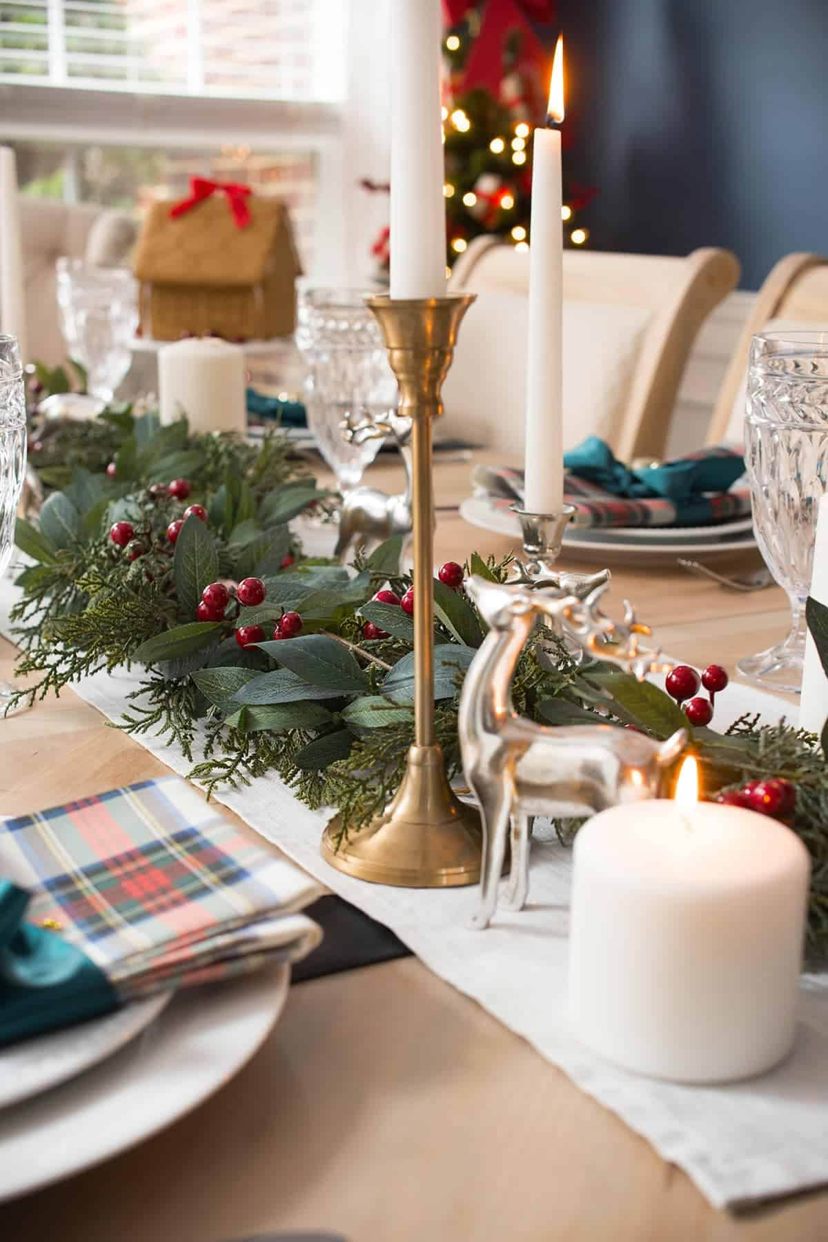 Christmas Table Centerpiece with Tartan plaid and red berry & bay leaf garland. Brass accents, white candles.