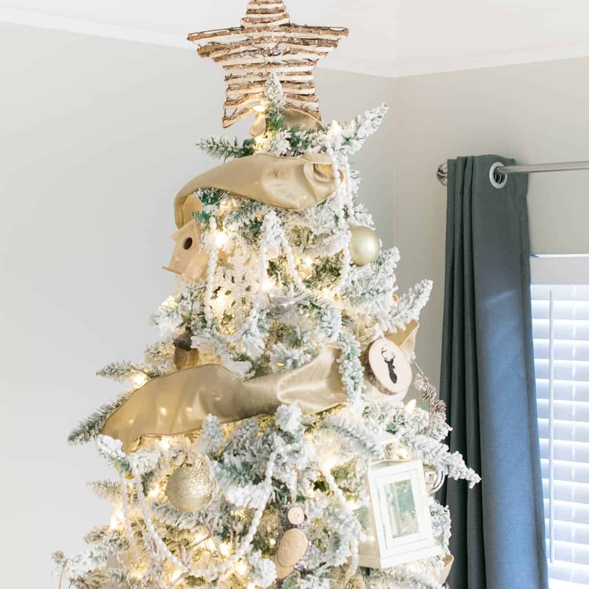 Close up of White Woodland Animals Tree with gold accents and star topper.