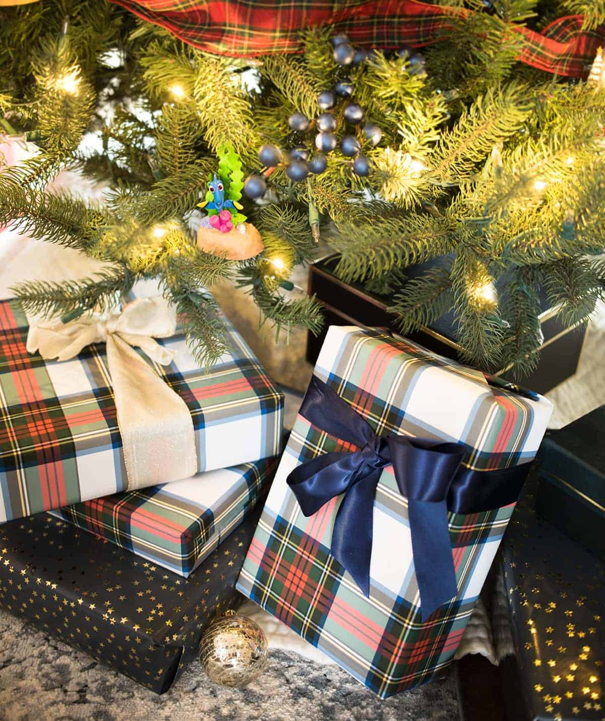 Tartan plaid wrapped Christmas Presents with fabric ribbon stacked among other gifts under the tree.