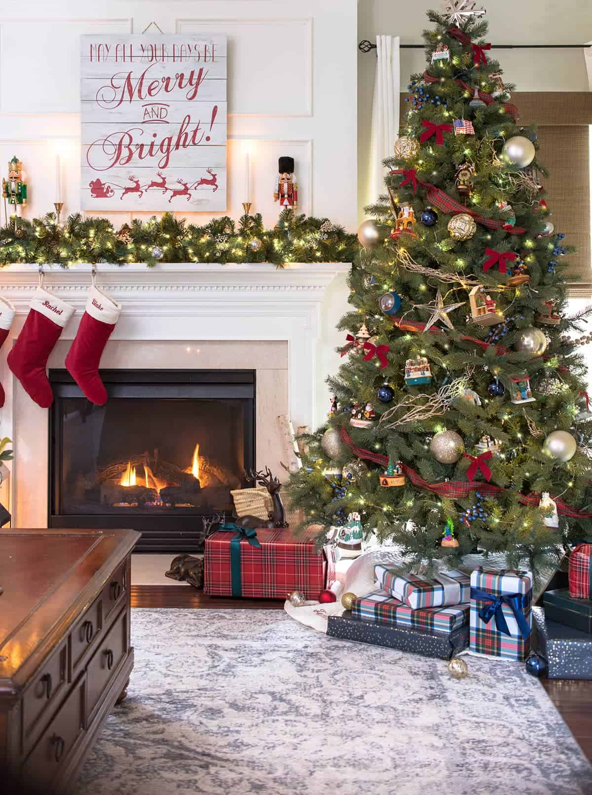 Traditional Tartan Plaid Christmas Tree Decorations in family room with fireplace aglow and presents stacked under tree.