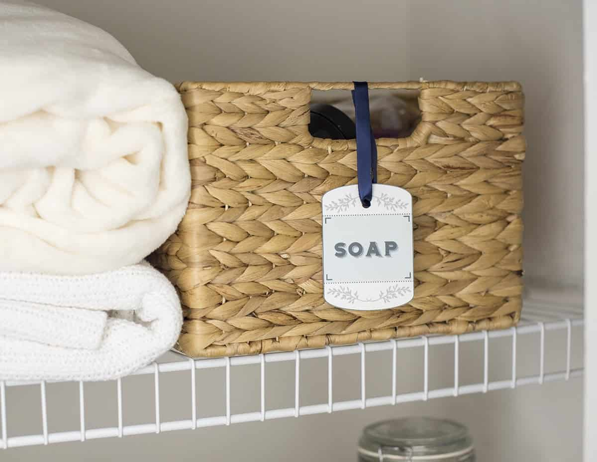 A label for soap on a hyacinth basket in an organized linen closet.
