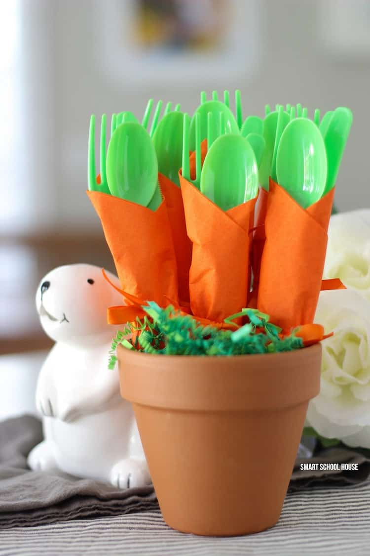 Clay pot filled with green Easter grass and green plasticware wrapped in orange napkins next to white bunny and flowers.