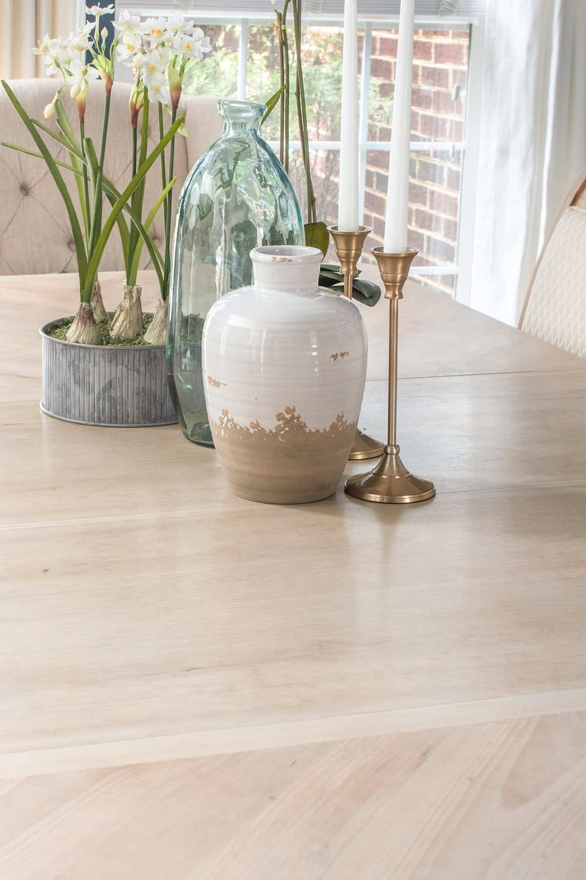 Photo of stained and top-coated dining room table in raw natural finish. Center piece items include paper whites, white & tan pottery jug, brass candlesticks.