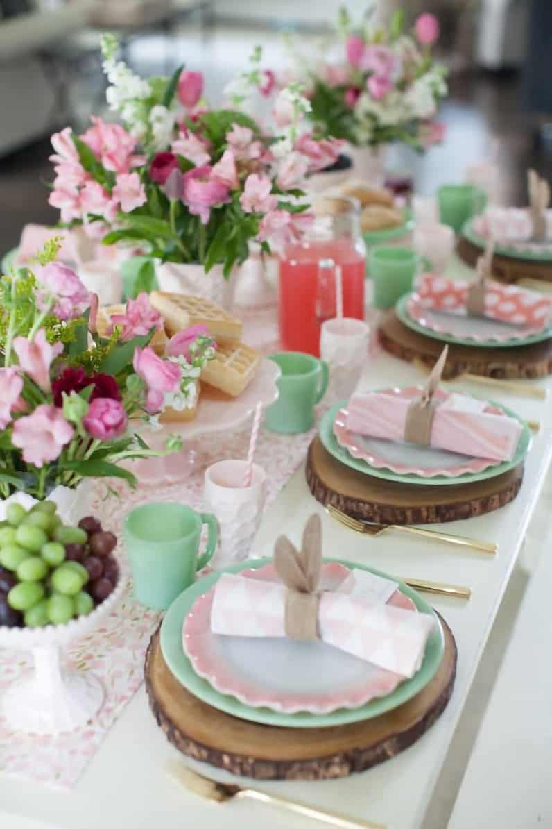 Feminine springtime table setting with green and pink color scheme with row of flower centerpieces.