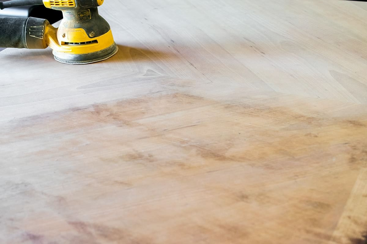 Electric sander removing remaining stain from surface of stripped table.