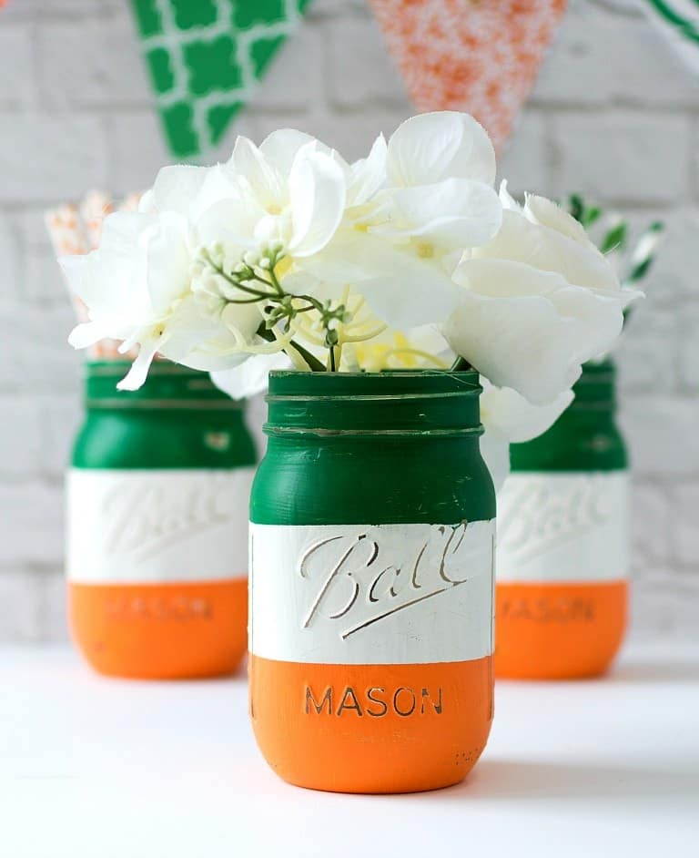 3 mason jars painted orange, green, and white filled with delicate white flowers on white surface with orange and green banner in background.