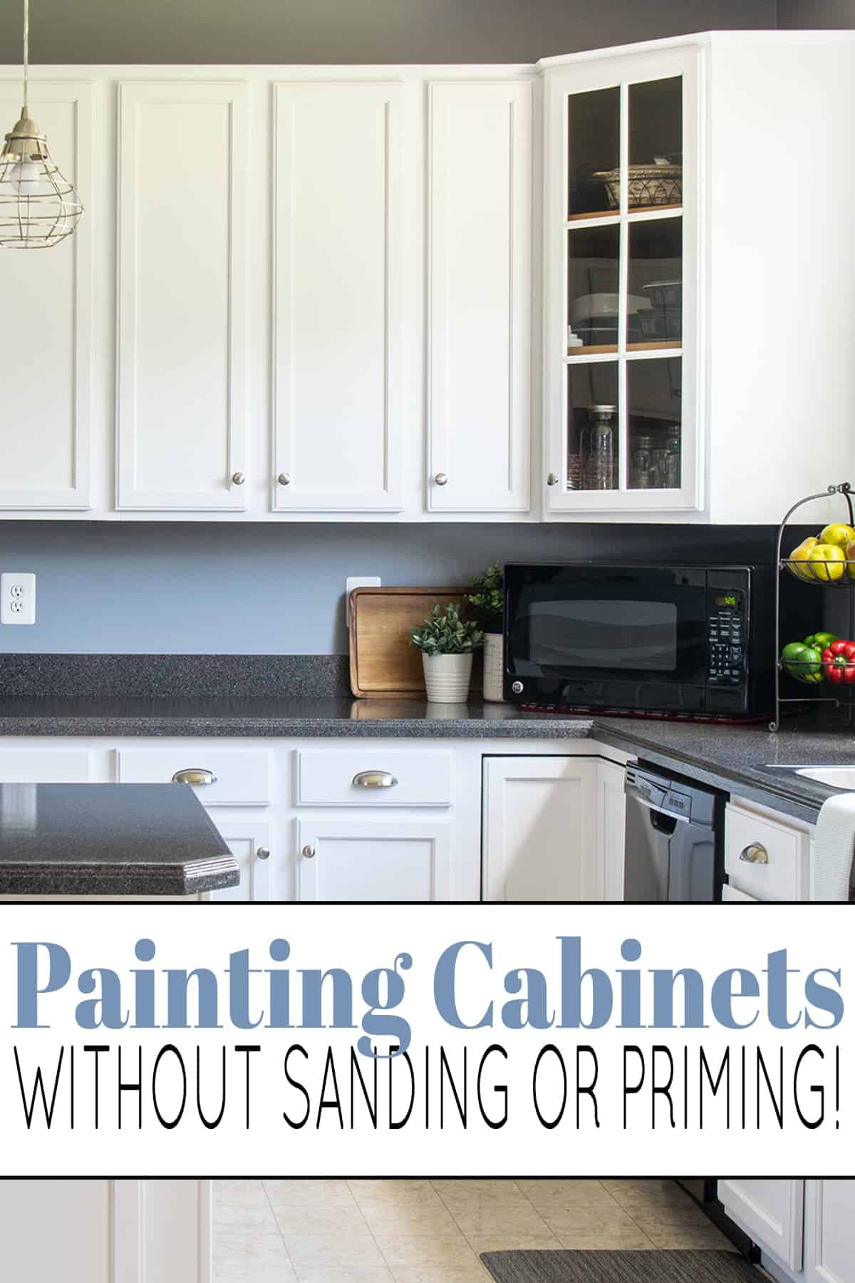 Traditional kitchen with white painted kitchen cabinet with glass door corner cabinet, dark gray countertops, with black microwave, fruit stand, and potted plants.
