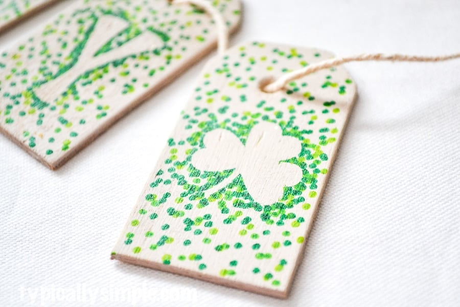 Green polka dotted tags with letters and shamrocks on rope for St. Patrick's day banner laying on white surface.