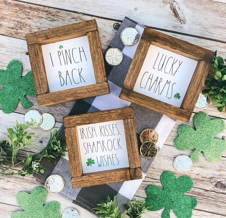Wood framed St. Patrick's day message art on black and white buffalo plaid towel with coins and sparkly shamrock cutouts on wooden planks.
