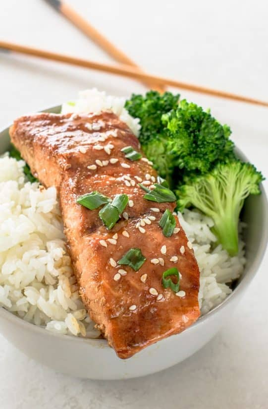 Fillet of salmon over rice and broccoli in a bowl with chopsticks in the background.