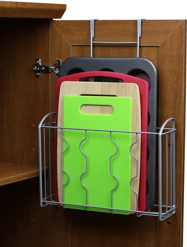 Wire rack holding cutting boards hung inside a cabinet door.
