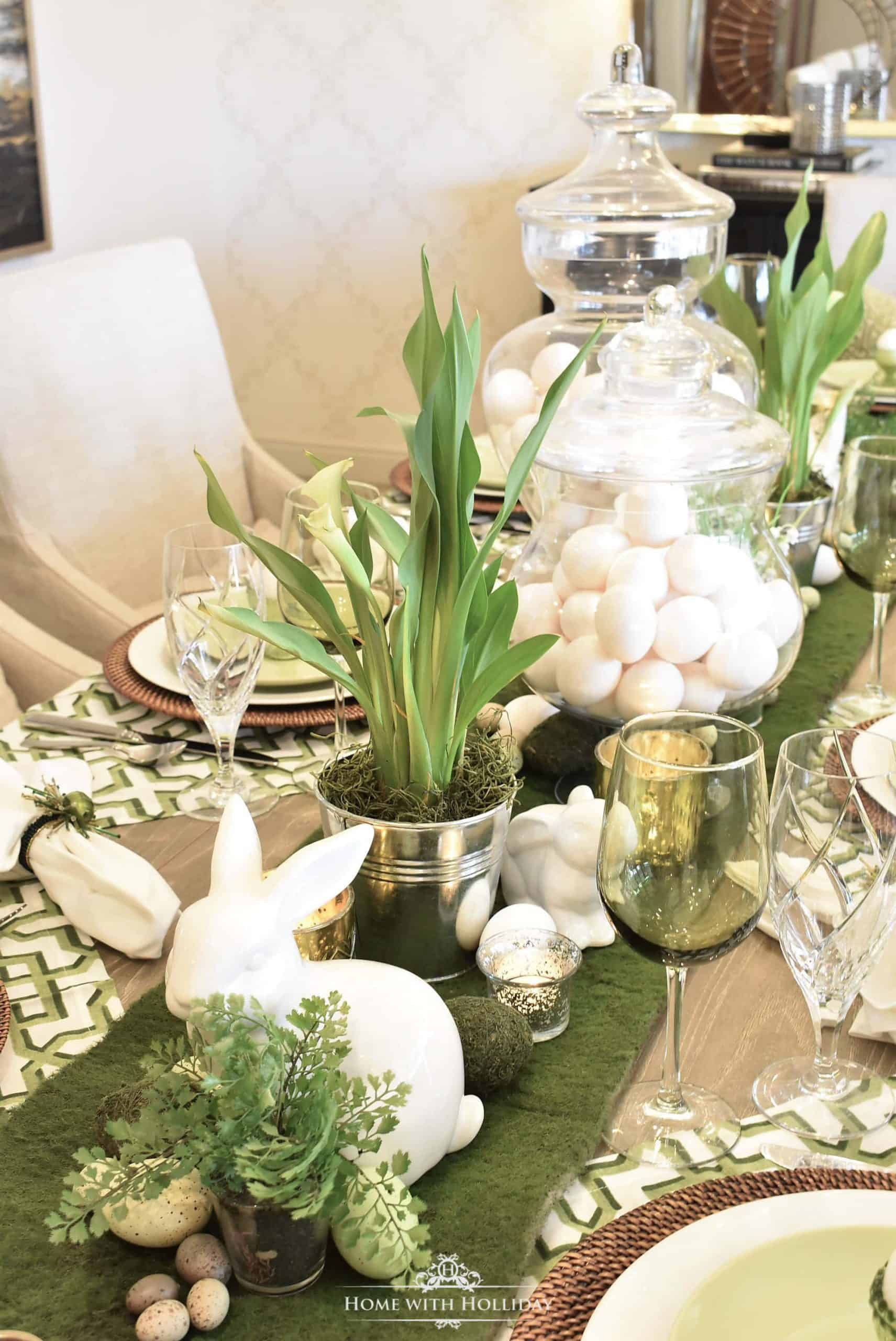 Elegant table setting with eggshell and green color scheme, green table runner, glass containers filled with eggs, and metal buckets with grass-like plants.
