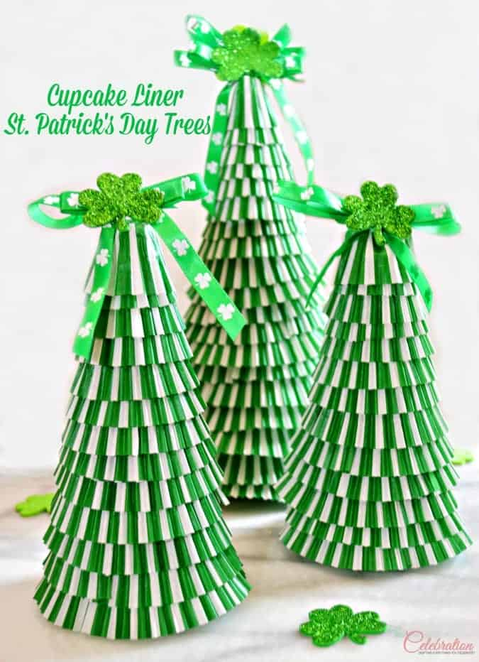 3 DIY tree crafts made of stacked green and white cupcake liners with shamrock ribbon and glittered shamrock tree toppers.
