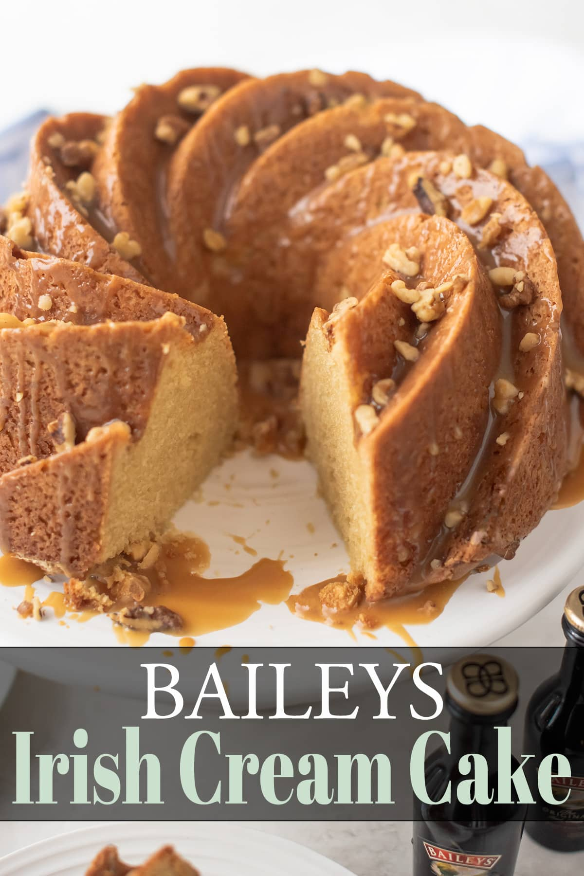 Bailey's Irish Cream Cake with slice cut out and Bailey's glaze and walnut topping cascading over top and sides. Bailey's bottles in distant forefront.