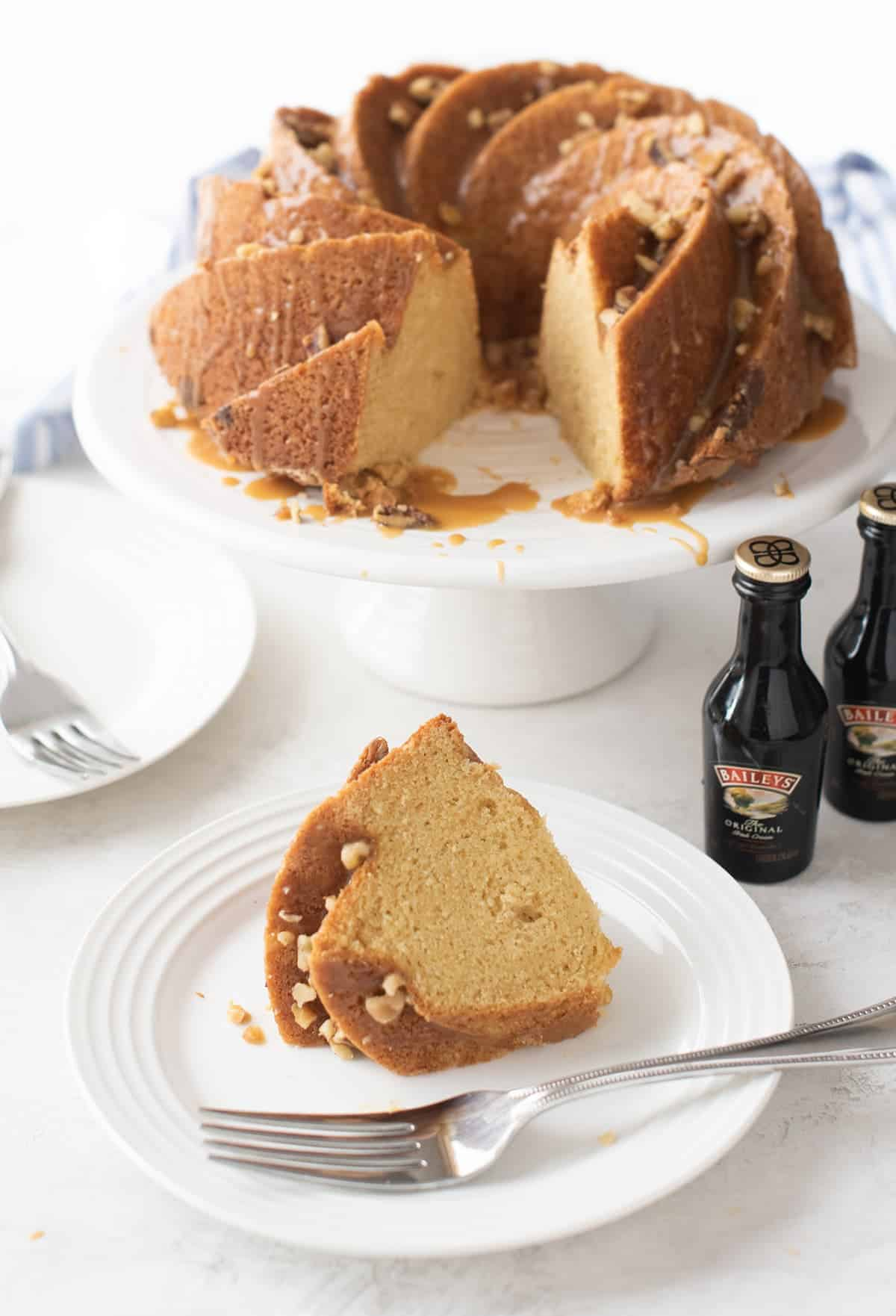Bailey's Irish Creme Cake perched on white cake stand with one slice removed. Two white cake plates in forefront of photo, one holds silver fork, one hold slice of Bailey's cake. Two miniature bottles of Bailey's Irish Creme liquor next to cake stand.